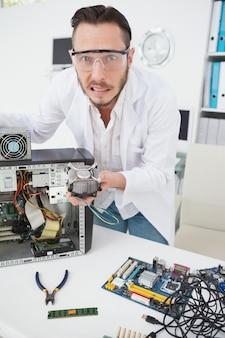Ingénieur en informatique stressé montrant un ventilateur brisé