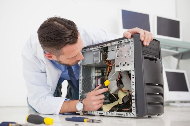 Ingénieur en informatique travaillant sur une console cassée avec un tournevis