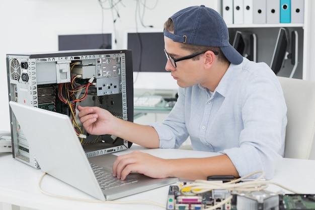 Ingénieur en informatique travaillant sur une console endommagée avec un ordinateur portable