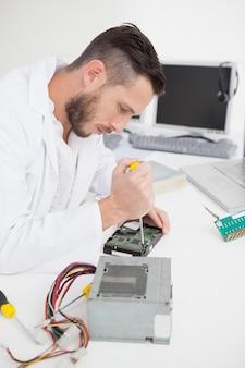 Ingénieur en informatique travaillant sur cpu cassé avec un tournevis