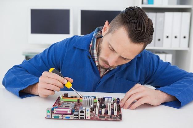 Ingénieur en informatique travaillant sur cpu avec un tournevis