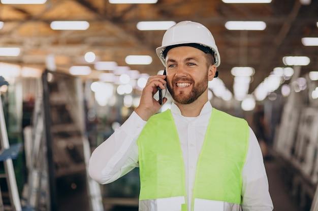 Ingénieur de jeune homme travaillant à l'usine faisant la commande au téléphone