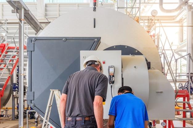 Ingénieur de maintenance travaillant avec une chaudière à gaz d'équipement de chauffage dans une chaufferie
