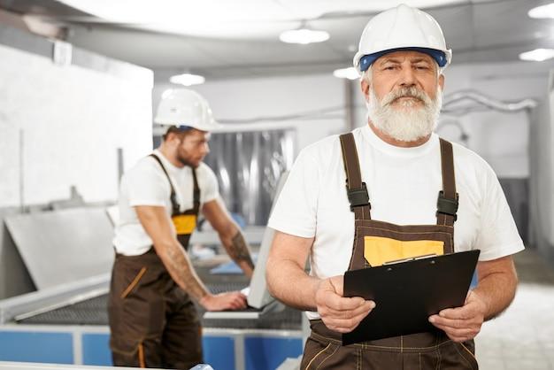 Ingénieur mâle en uniforme et dossier de tenue de casque