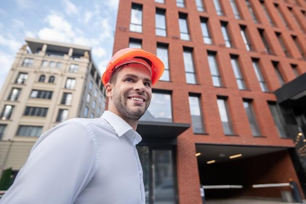 Ingénieur masculin en casque orange souriant et à la confiance