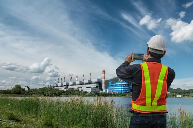 Ingénieur masculin vérifiant et contrôlant avec la centrale électrique au charbon.