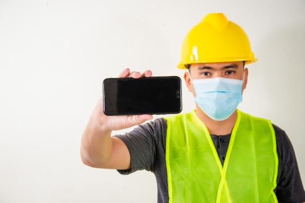 Ingénieur en masque médical tenant un smartphone.