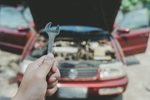 Un ingénieur en mécanique ouvre la jupe de la voiture pour vérifier le niveau d'huile de la voiture.