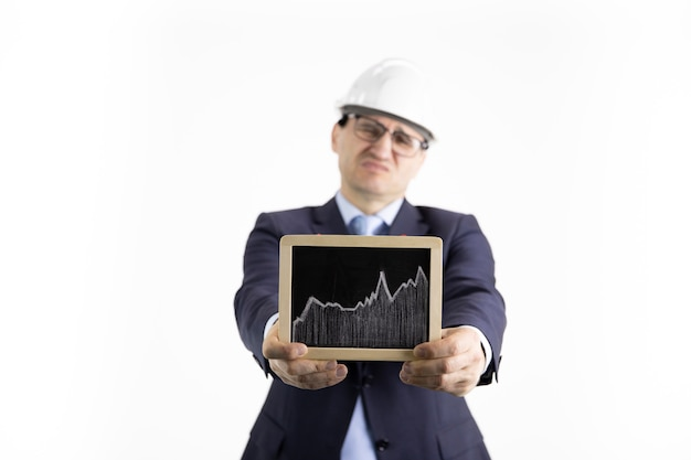 Un ingénieur mécontent tient une pancarte avec un graphique en hausse de l'industrie de la raffinerie