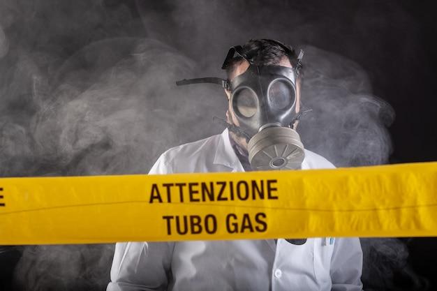 Un ingénieur médical portant un masque antigaz expérimenté dans la crise des fuites de gaz dirige l'urgence pendant le chaos. sur le ruban jaune la mention écrite