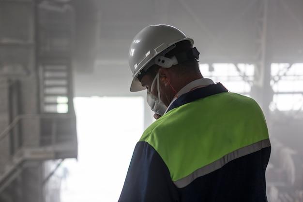 Un ingénieur des mines dans un casque blanc et un respirateur inspecte un atelier sale poussiéreux