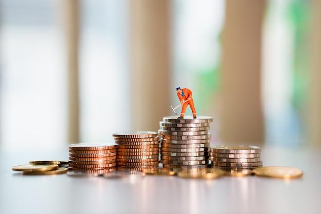 Ingénieur miniature portant un costume orange sur des pièces de pile