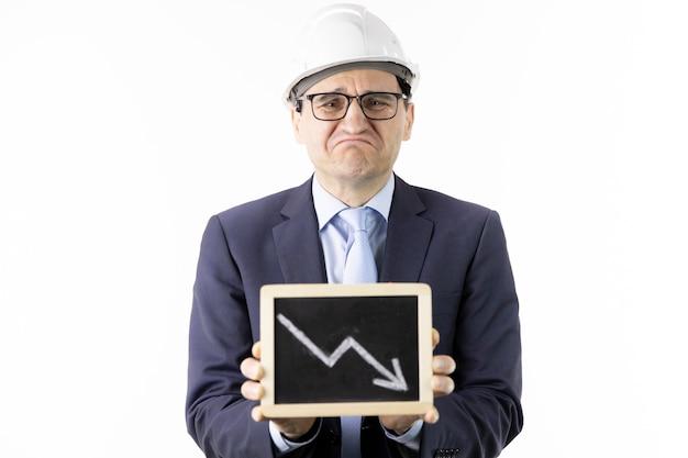 Ingénieur minier déprimé détient une tablette avec des flèches vers le bas