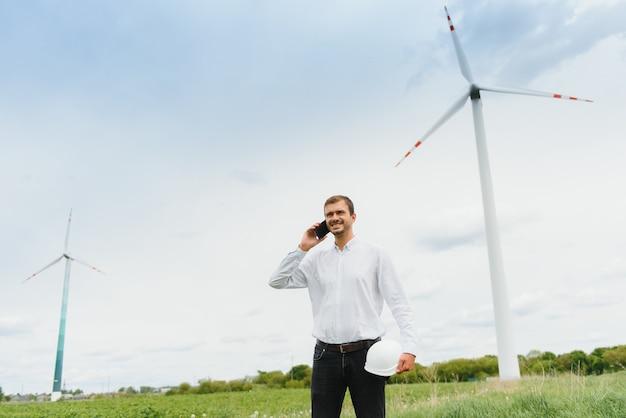 Ingénieur de moulin à vent parlant au téléphone sur moulin à vent. un homme en casque supervise le fonctionnement des moulins à vent électriques.