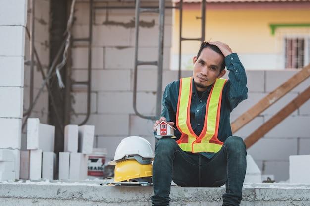 Ingénieur ouvrier architecte assis sur le chantier maison de construction de travaux de construction