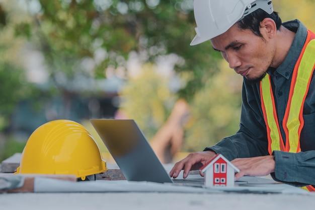 Ingénieur ouvrier architecte travaillant sur la construction de son site pour ordinateur portable