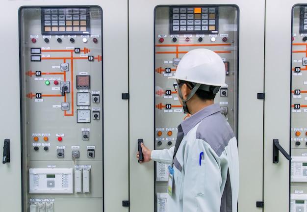 Ingénieur et panneau de contrôle et de protection 115kv dans la centrale électrique