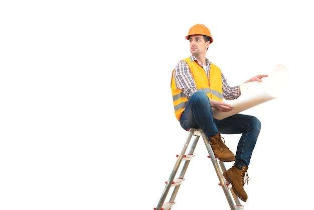 L'ingénieur avec un papier assis sur l'échelle sur fond blanc