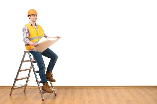 L'ingénieur avec un papier debout sur l'échelle sur fond de mur blanc