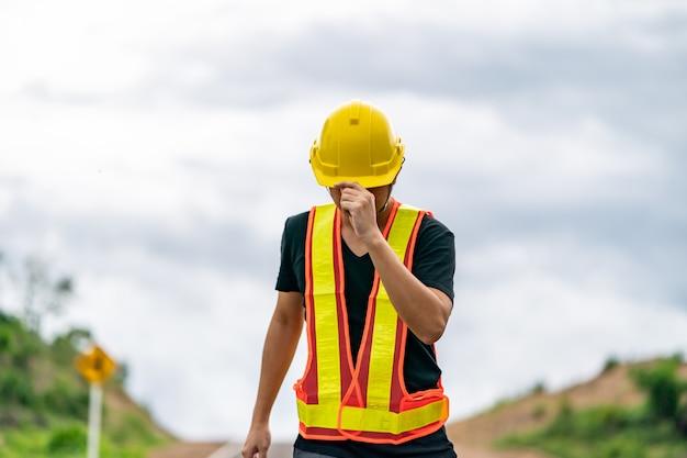 Ingénieur portant un casque jaune, contrôlant la construction.