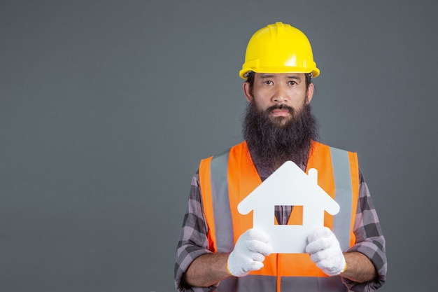Un ingénieur portant un casque de sécurité jaune portant un symbole de maison blanche sur un gris.