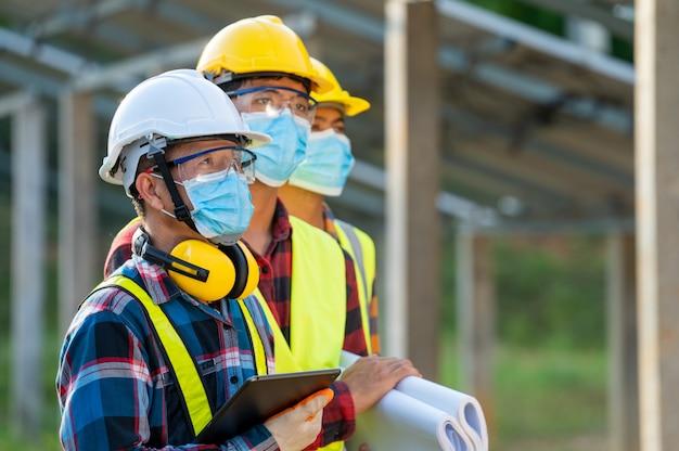 Ingénieur portant un masque de protection pour se protéger contre covid-19 travaillant sur la vérification et la maintenance dans une centrale solaire, une centrale solaire, l'énergie solaire scientifique.