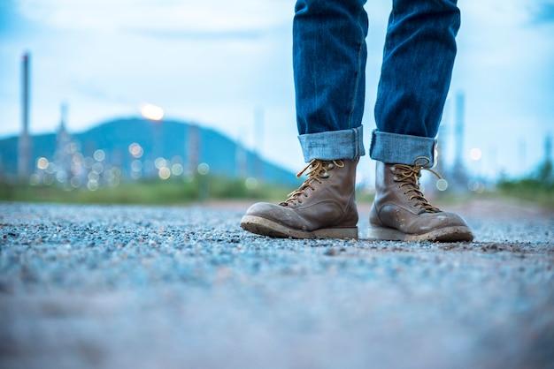 L'ingénieur porte des jeans et des bottes marron pour la sécurité des travailleurs sur fond de raffinerie.