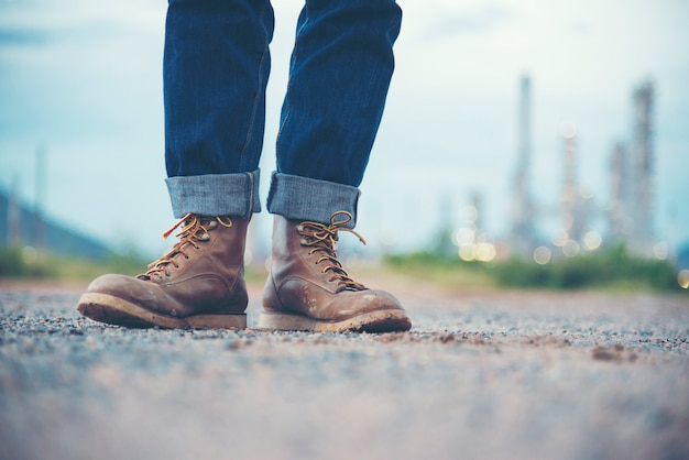 Ingénieur porter des jeans et des bottes marron pour la sécurité des travailleurs sur fond de raffinerie
