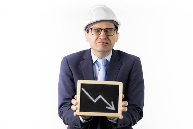 Ingénieur qui pleure dans un casque détient une tablette avec des flèches vers le bas