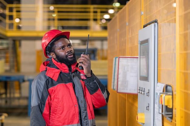Ingénieur réparateur noir barbu sérieux en casque à l'aide de talkie-walkie tout en faisant des rapports sur le processus de la machine