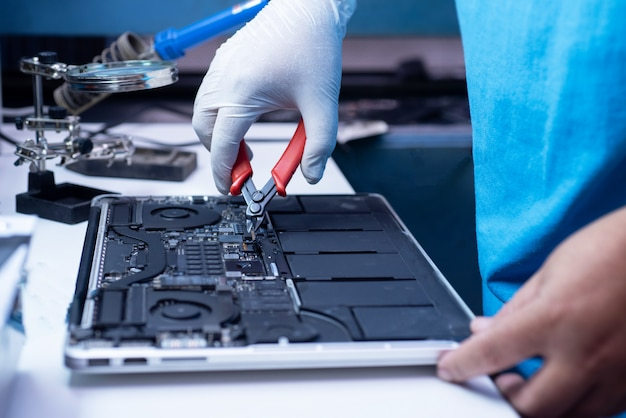 L'ingénieur répare l'ordinateur portable et la carte mère.