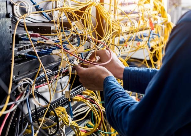 Ingénieur réseau travaillant dans la salle des serveurs. connexion des câbles réseau aux commutateurs