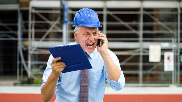 Ingénieur senior en colère criant au téléphone