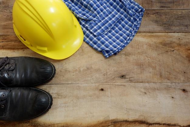 Ingénieur sertie de chaussures de sécurité, casque, chemise sur fond de bois
