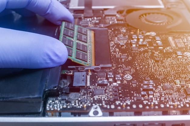 L'ingénieur de service installe de nouvelles puces de mémoire ram sur l'ordinateur portable
