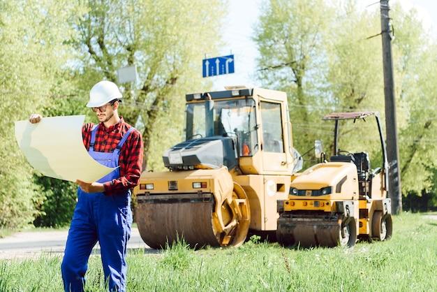 Ingénieur souriant avec casque debout devant une pelle sur le chantier de construction de routes