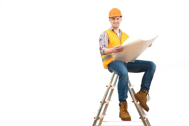 L'ingénieur de sourire avec un papier se reposant sur l'échelle sur le fond blanc