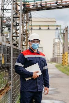 Un ingénieur de sous-station électrique inspecte les équipements haute tension modernes dans un masque au moment de la pandémie. énergie. industrie.