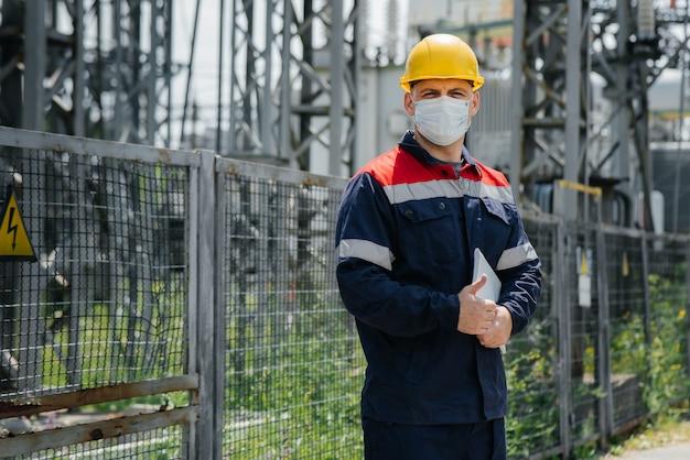 Un ingénieur de sous-station électrique inspecte les équipements haute tension modernes dans un masque de protection.