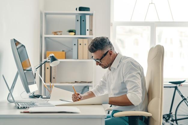 Ingénieur à succès. beau jeune homme dessinant quelque chose alors qu'il était assis au bureau