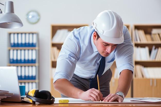 Ingénieur superviseur travaillant sur des dessins au bureau