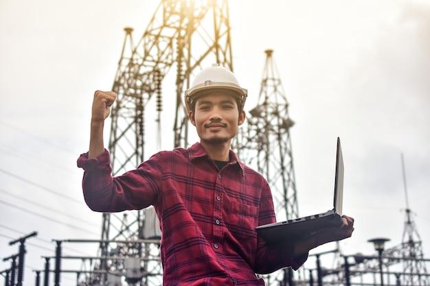 Ingénieur tenant un ordinateur portable sur le système haute tension de la centrale électrique du site