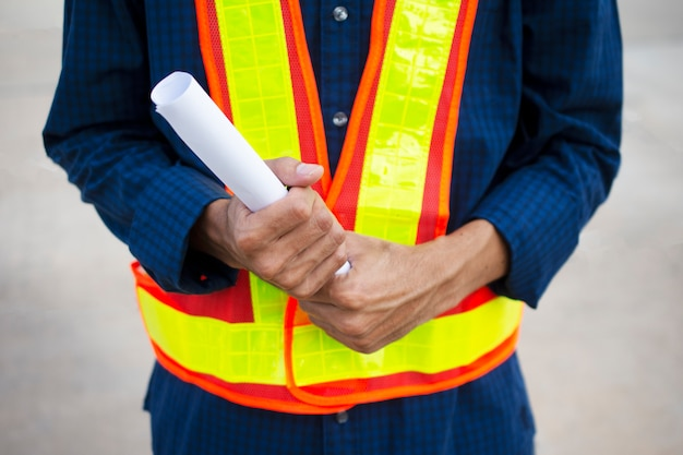 Ingénieur tenant un plan en papier pour le travail de rabotage