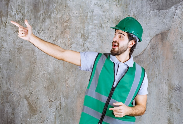 Ingénieur en tenue jaune et casque debout sur un mur de béton et interagissant avec la personne devant.