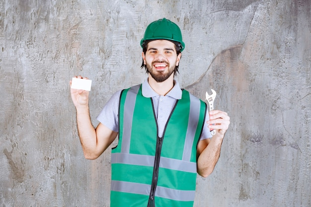 Ingénieur en tenue jaune et casque tenant une clé métallique et présentant sa carte de visite.