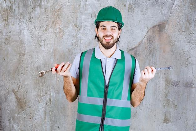 Ingénieur en tenue jaune et casque tenant une clé métallique.