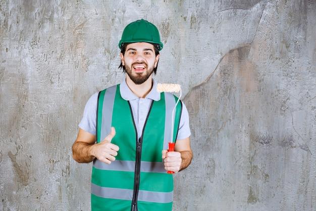 Ingénieur en tenue jaune et casque tenant un rouleau de finition et montrant le pouce vers le haut.