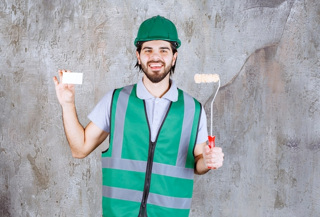 Ingénieur en tenue jaune et casque tenant un rouleau de finition et présentant sa carte de visite.