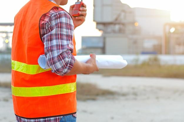 Ingénieur travaillant en extérieur avec la radio du groupe de citoyens et plan sur le chantier