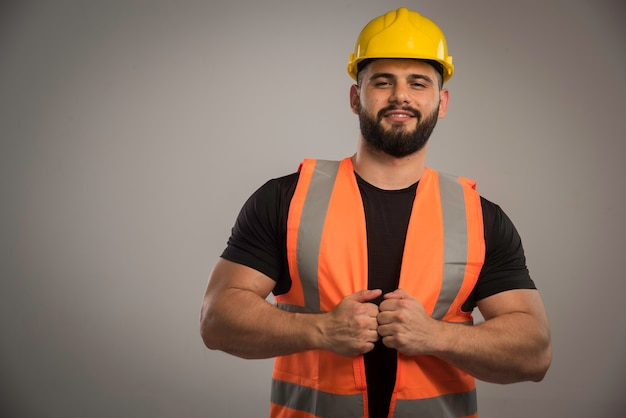 Ingénieur en uniforme orange et casque jaune a l'air confiant